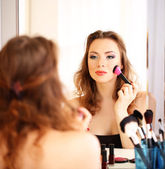 Young beautiful woman making make-up near mirror — ストック写真