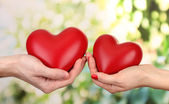 Red hearts in woman and man hands, on green background — Stock Photo