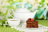 Teapot, cup of tea and delicious cake on natural background — Stock Photo
