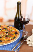 Tasty pizza with wine on wooden table on room background close-up — Stock Photo