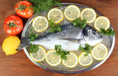 Fresh fish of dorado on tray with lemon and parsley on wooden table — Stock Photo