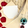 Old envelope with blank paper and dried rose petals on music sheets close up — Stock Photo #21232373