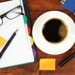 Cup of coffee on worktable covered with documents close up — Foto Stock