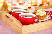 Cups of tea with cakes on wooden tray on table in cafe — Stock Photo