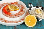 Shrimps with lemon on plate on blue wooden table close-up — Stock Photo