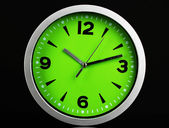 Round office clock on black background — Stock Photo