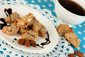 Aromatic cookies cantuccini on plate with cup of coffee on blue tablecloth close-up — Stock Photo