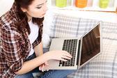 Piękna młoda kobieta pracuje na laptopie na kanapie w pokoju — Zdjęcie stockowe