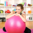 Young woman with gym ball at home — Stock Photo