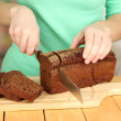 Woman slicing black bread on chopping board on wooden table close up — Stock Photo #21284337