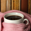 Cup of coffee wrapped in scarf on books background — Stock Photo #21284785