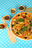 Tasty pizza on blue tablecloth close-up — Stock Photo