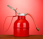 Oil can on red background — Stock Photo