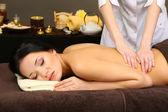Mulher jovem e bonita no salão spa recebendo massagem, em fundo escuro — Fotografia Stock
