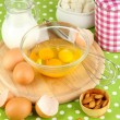 Broken egg in bowl and various ingredients next to them on green tablecloth close-up - Stock Photo