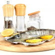 Fish in foil with herbs and lemon on board isolated on white — Stock Photo