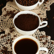 Different types of coffee in three cups on wooden table — Stock Photo