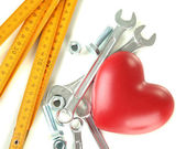 Heart and tools. Concept: Renovation of heart. Isolated on white — Zdjęcie stockowe