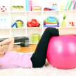 Young woman doing fitness exercises with gym ball at home — Stock Photo