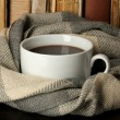 Cup of coffee wrapped in scarf on books background — Stock Photo #21358465