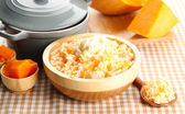 Taste rice porridge with pumpkin in bowl on tablecloth background — Stock Photo