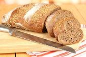 Vicino a fette di pane con semi di sesamo e coltello sul tagliere sul tavolo di legno — Foto Stock