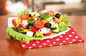 Tasty Greek salad on table in cafe — Stock Photo
