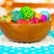 Dried oranges, wicker balls and other home decorations in wooden bowl, on bright background — Foto de Stock