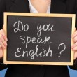 Stock Photo: Young womholding sign Do you speak english?