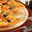 Tasty pizza with wine on wooden table close-up - Zdjęcie stockowe