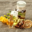 Bottles with ingredients for the perfume on burlap background - Stock Photo