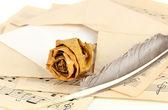 Gamla kuvert med blankt papper med torkad ros på musik ark på nära håll — Stockfoto