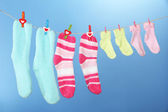 Colorful socks hanging on clothesline, on color background — Stock Photo