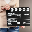 Movie production clapper board in hands on grey background - Stok fotoraf
