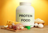 Jar of protein powder and food with protein, on yellow background — Stock Photo