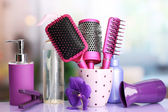 Hair brushes, hairdryer, straighteners and cosmetic bottles in beauty salon — Stock Photo