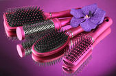 Comb brushes and flower on purple background — Stock Photo
