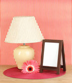 Brown photo frame and lamp on wooden table on red striped wall background — Stock Photo