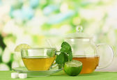 Cup of tea with mint and lime on table on bright background — Stock Photo