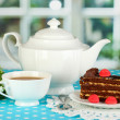 Teapot, cup of tea and delicious cake on window background — Stock Photo