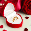 Beautiful box with wedding ring and rose on red silk background — Stock Photo