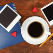 Cup of coffee on worktable covered with photo frames close up — Stock Photo