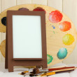 Photo frame as easel with artist's tools on wooden background — Zdjęcie stockowe