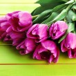 Beautiful bouquet of purple tulips on green wooden background — Stock Photo #21506377