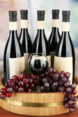 Composition of wine bottles, glass and grape,on wooden barrel, on bright background — Stock Photo