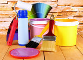 Paint pots, paintbrushes and coloured swatches on wooden table on stone wall background — Stock Photo