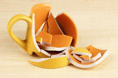Yellow broken cup on wooden background — Stock Photo