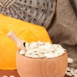 Pumpkin seeds in wooden bowl, on sackcloth background - Stock Photo