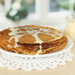 Sweet pancakes on plate with condensed milk on table in kitchen - Stock Photo