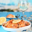 Shrimps with lemon on plate on wooden table on blue natural background — Stock Photo